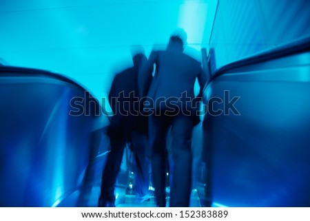 businesspeople on escalator in motion