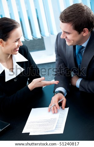 Businesspeople or business person and client, with document at office