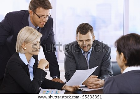 Businesspeople reviewing contract at meeting in office.?