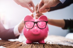 Businesspeople's Hand Inserting Coins Into Pink Piggybank In Office