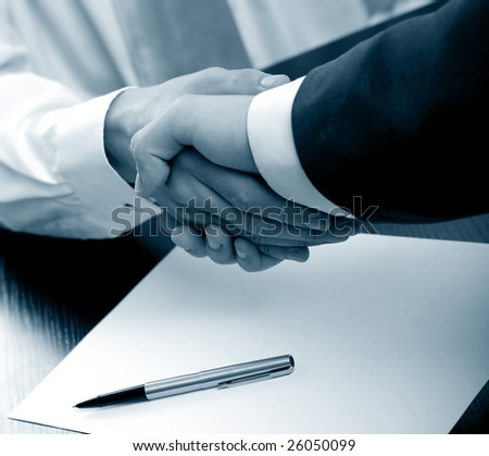 Businesspeople shaking hands. blue tone