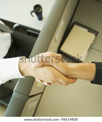 Businesspeople shaking hands over cubicle wall