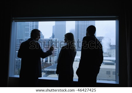 Businesspeople silhouetted in front of a large window that overlooks the city. Horizontal shot.