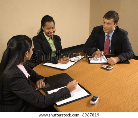 Businesspeople sitting at conference table talking and smiling.