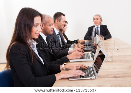 Businesspeople Sitting At Conference Table Using Laptop