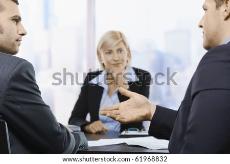 Businesspeople sitting at table in office, discussing work at meeting. Focus on explaining hand.?