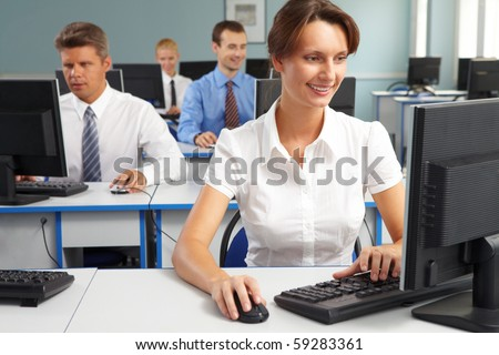 Businesspeople sitting at tables and looking at their monitors with smiling woman at foreground