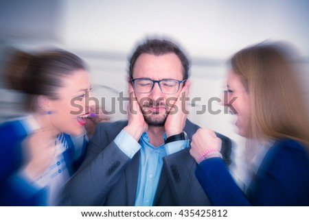 Businesspeople sitting at the office desk. Annoyed businessman covering his ears with hands and two women yelling at him from his left and right side.