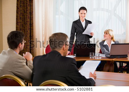 Businesspeople sitting at the table listening to their colleague's speech in conference room
