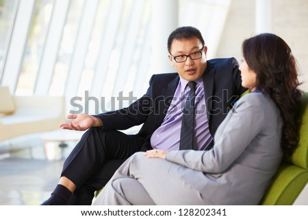 Businesspeople Sitting On Sofa In Modern Office