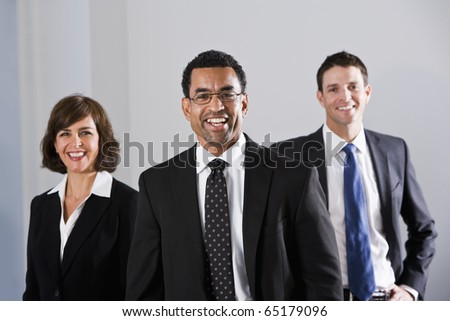 Businesspeople standing in office, focus on African American businessman, 40s