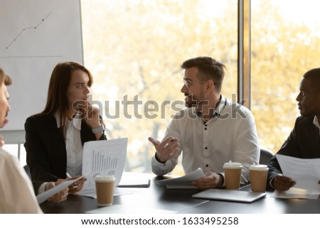 Businesspeople talking discussing business project at multi-ethnic board meeting in modern conference room, multinational employees work together analysing financial report at corporate group briefing