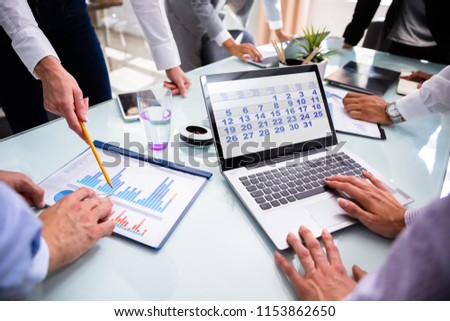 Businesspeople Using Calendar On Laptop While Analyzing Graphs Over Desk #1153862650