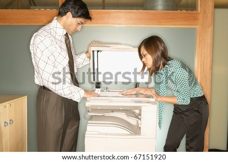 Businesspeople using copy machine