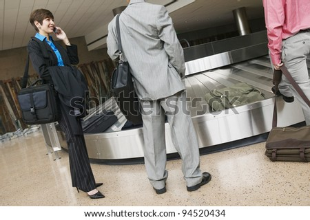 Businesspeople waiting for luggage at airport