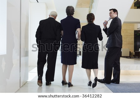 Businesspeople walking in a corridor to a meeting.