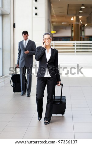 businesspeople walking in airport with luggage - stock photo