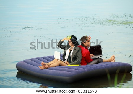 Businesspeople with notebook sitting on inflatable mattress and looking at different way