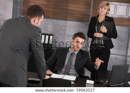 Businesspeople working in office, boss sitting at desk pointing at laptop computer screen, colleagues standing around.?