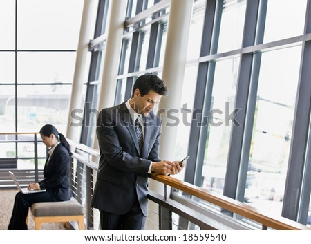 Businesspeople working on laptop and text messaging in office lobby
