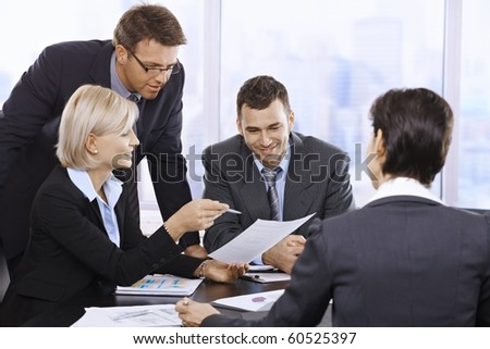Businesspeople working together at meeting table in office.?