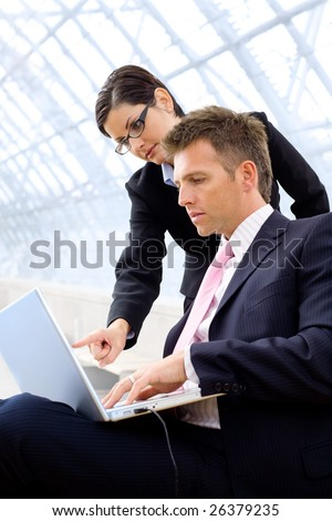 Businesspeople working together, using laptop computer at office lobby.