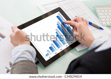 Businessperson Analyzing Graph On Digital Tablet In The Office