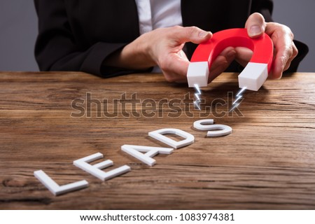 Businessperson Attracting White Lead Text With Horseshoe Magnet Over Wooden Desk #1083974381
