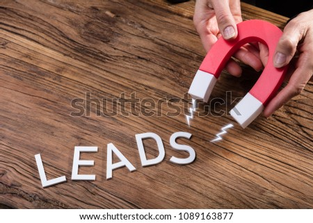 Businessperson Attracting White Lead Text With Horseshoe Magnet Over Wooden Desk #1089163877