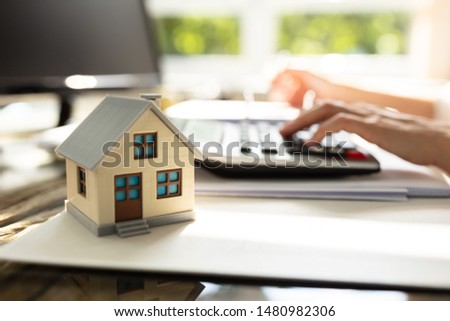 Businessperson Calculating Invoice In Front Of House Model Over Desk