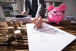 Businessperson Calculating Invoice With Piggybank And Golden Coins On Desk