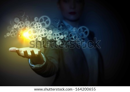 Businessperson holding gears and cogwheels in palm