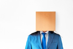 Businessperson in a blue suit, shirt, tie with a carton box on his head on a white background. Be different, out of the box thinking, Narrow-mindedness, isolation concept.