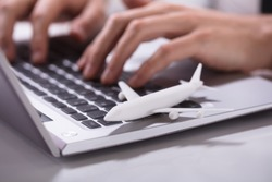 Businessperson's Hand Using Laptop With Airplane Over Desk