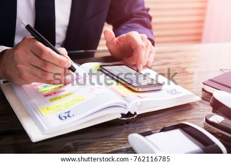 Businessperson Using Mobile Phone With Diary On Desk