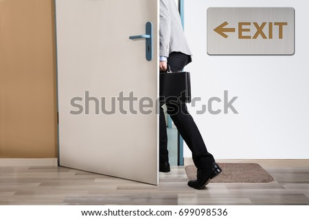Businessperson Walking Out With Exit Sign On Wall
