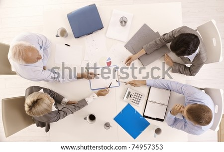 Businessteam busy working at meeting table, pointing at document, overhead view.?