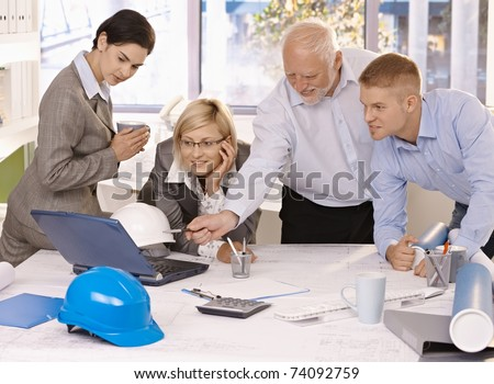 Businessteam discussing designer work on laptop computer, experienced architect pointing at screen.?