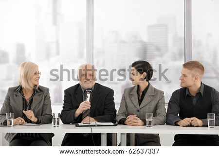 Businessteam on meeting, senior executive talking into microphone giving speech, smiling.?