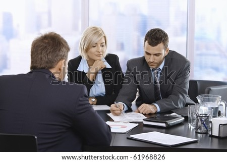 Businessteam reviewing documents together at meeting in office.?