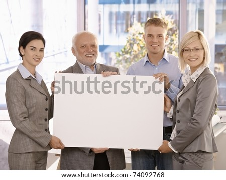 Businessteam standing in office, smiling, holding blank poster for copy space.?