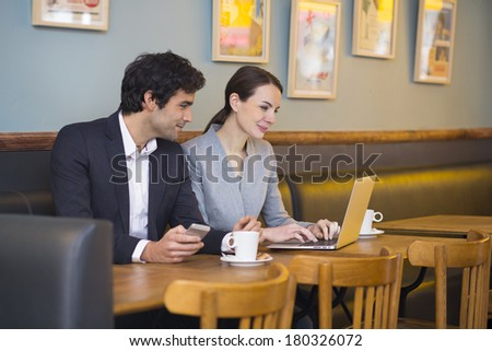 Businessteam working on laptop at coffee bar
