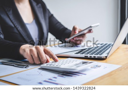 Businesswoman accountant working analyzing and calculating expense financial annual, financial balance sheet statement and analyze document graph and diagram, doing finance making notes on report.
