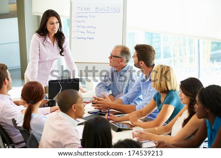 Businesswoman Addressing Meeting Around Boardroom Table stock photo