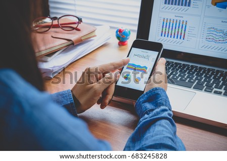 Businesswoman analyzing financial data on smartphone and computer screen.Close up Foto stock ©