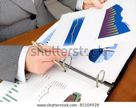 Businesswoman analyzing investment charts at his workplace