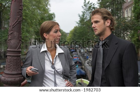 Businesswoman and businessman having a conversation outdoors; at an Amsterdam channel