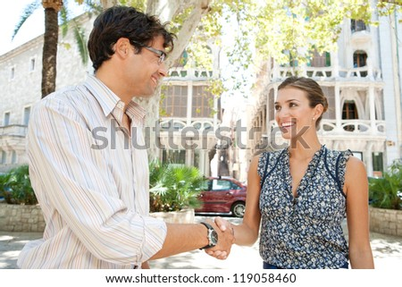Businesswoman and businessman shaking hands while standing in a classic city square, smiling outdoors.