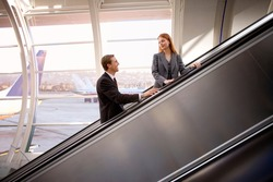 Businesswoman and businessman standing on an escalator and looking at each other on and escalator in the airport