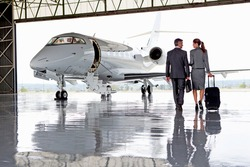 Businesswoman and Businessman walking towards a private jet
